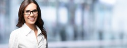 Portrait of happy smiling beautiful young businesswoman in glasses, over blured office background, with blank copy space for some slogan or text. Horizontal banner composition picture.