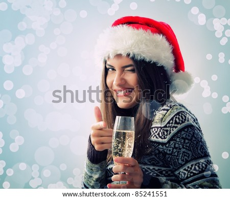 portrait of happy smiling beautiful young christmas woman winks with santa's hat and glass of champagne over blue snow background