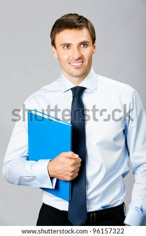 Portrait of happy smiling business man with blue folder, over gray background