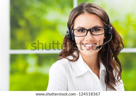 Portrait of happy smiling cheerful beautiful young support phone operator in headset, at office, with copyspace