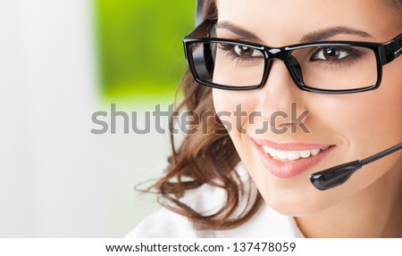 Portrait of happy smiling cheerful beautiful young support phone operator in headset, with copyspace