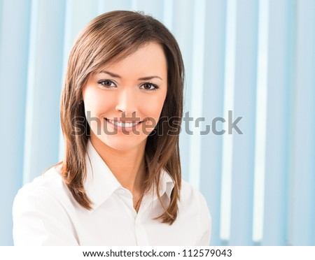 Portrait of happy smiling cheerful business woman at office - stock photo