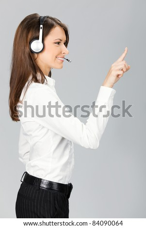 Portrait of happy smiling cheerful customer support phone operator in headset pointing at something, over grey background