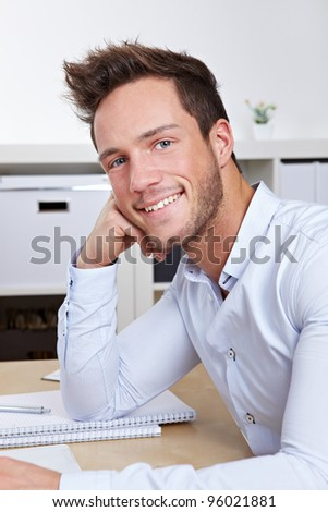 Portrait of happy smiling college student sitting at desk