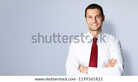 Portrait of happy smiling confident businessman in red tie, with crossed arms pose, empty copy space place for some text, advertising or slogan, standing against grey background