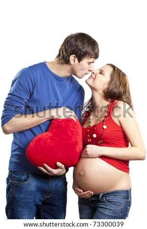 Portrait of happy smiling couple holding pregnant belly and red heart with hands