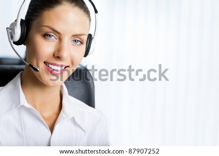 Portrait of happy smiling customer support phone operator in headset at office. You can use right part for slogan, big text or banner.