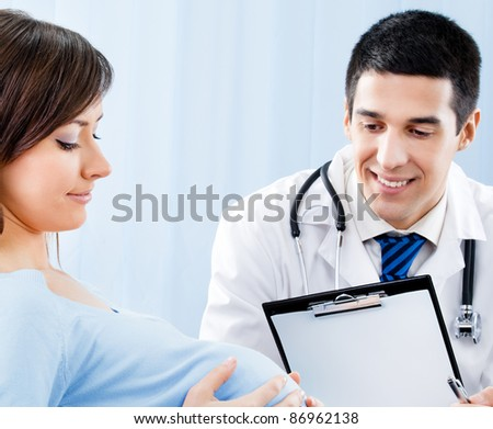 Portrait of happy smiling doctor and pregnant young woman, at office
