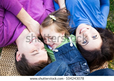 Portrait of happy smiling family lying outdoors in autumn park