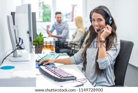 Portrait of happy smiling female customer support phone operator at workplace. #1149728900