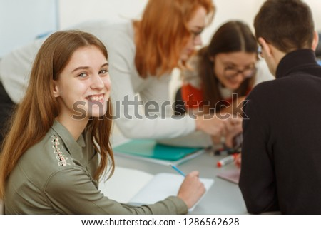 Portrait of happy smiling girl with long hair sitting near table. Students communicating and discussing interesting topic. Pupils during interactive lessons in private school of foreign languages. #1286562628