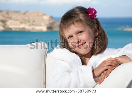 Portrait of happy smiling little girl with flowered hair in white bathrobe relaxing on terrace divan and looking at camera on the sea background