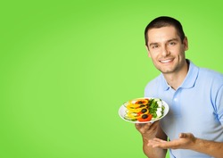 Portrait of happy smiling man in blue casual clothing, with plate of salad, posing at studio, over green background, with copy space area. Dieting and healthy eating concept.