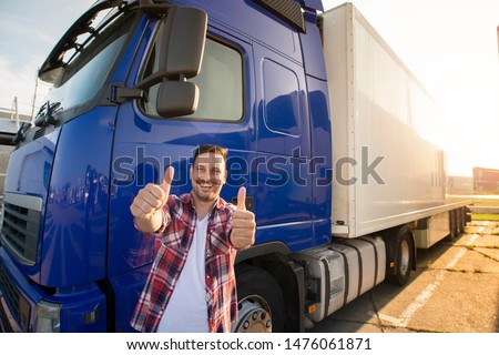 Portrait of happy smiling middle aged truck driver standing by his truck and holding thumbs up. Successful transportation service. #1476061871