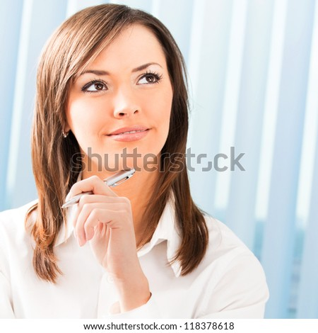 Portrait of happy smiling thinking business woman at office