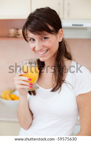 Portrait of happy smiling woman drinking fresh orange juice in the kitchen - stock photo