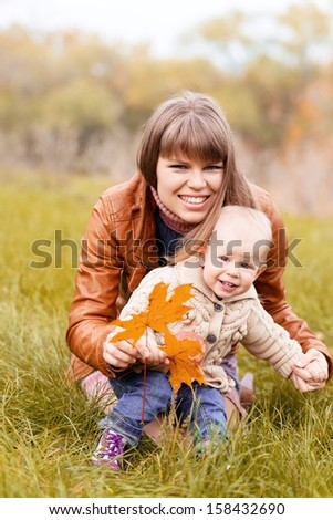 Portrait of happy smiling woman holding her cute blond child outdoors. Pretty mother and her toddler girl playing with autumn yellow leaves.