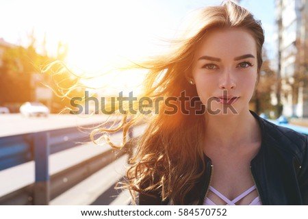 Portrait of happy smiling woman standing on the square on sunny summer or spring day outside, cute smiling woman looking at you, attractive young girl enjoying summer, filtered image, flare sunshine