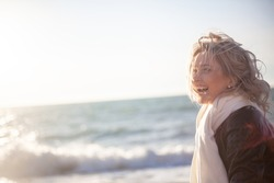 Portrait of happy smiling woman walking outdoor in the sea shore beach on wind weather against the sun lights.