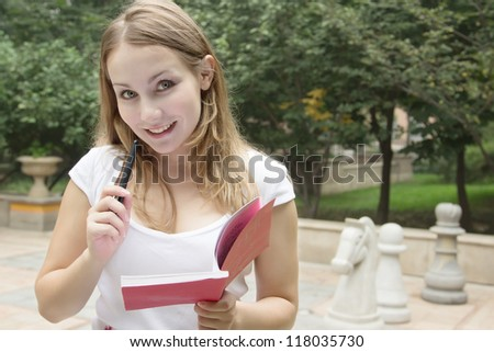 Portrait of happy smiling woman with book on green background with chessmen playground of city park