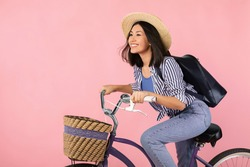 Portrait of happy smiling young asian woman riding classic bicycle with wicker basket. Casual positive lady wearing summer hat, black backpack bag looking away isolated over pink color background