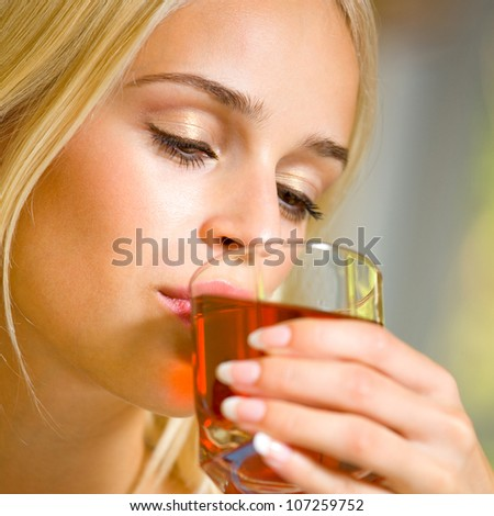 Portrait of happy smiling young beautiful blond woman drinking garnet juice