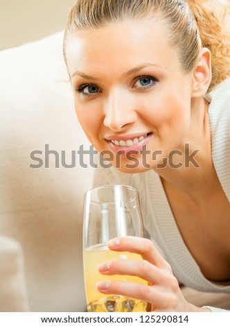 Portrait of happy smiling young beautiful blond woman drinking orange juice