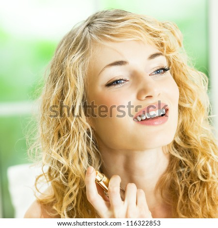 Portrait of happy smiling young beautiful blond woman with perfum bottle at home