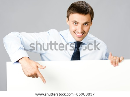 Portrait of happy smiling young business man showing blank signboard, over gray background - stock photo