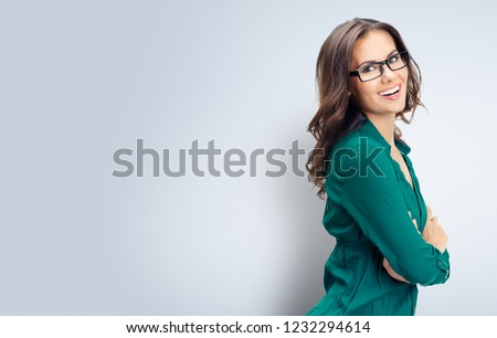 Portrait of happy smiling young business woman in green confident clothing and glasses, empty copyspace place for slogan or some advertising text message, over grey background.
