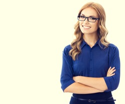 Portrait of happy smiling young cheerful businesswoman in blue clothing and glasses in crossed arms pose