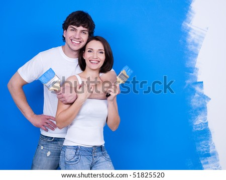 Portrait of happy smiling young couple with paintbrushes
