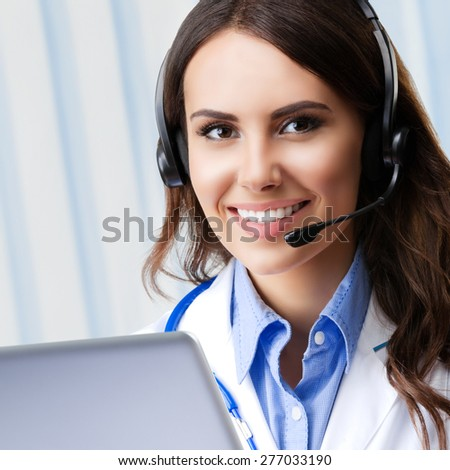 Portrait of happy smiling young doctor in headset, using laptop, with blank copyspace area for slogan or text