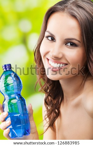 Portrait of happy smiling young woman with water bottle, outdoor
