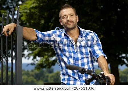 Portrait of happy, stubbly, caucasian, casual man on bicycle outdoor, leaning against fence. Smiling.