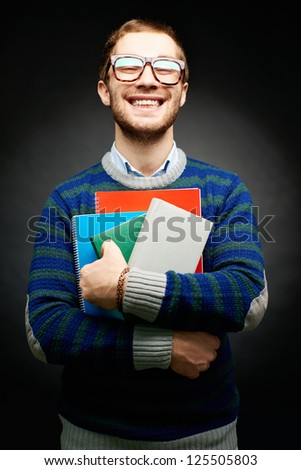 Portrait of happy student in eyeglasses holding books