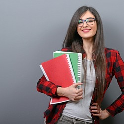 Portrait of happy student woman holding books against gray background