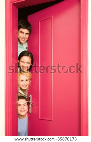 Portrait of happy students looking from behind door at camera with smiles