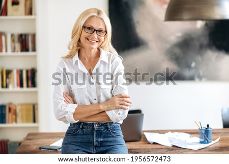 Portrait of happy successful elegant middle aged caucasian woman, stylishly dressed, with glasses, standing near the table, with arms crossed, looking at camera, smiling friendly. Photo stock ©