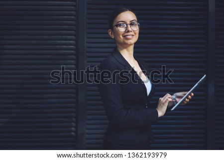 Portrait of happy successful female employee looking at camera while holding modern digital gadget and smiling on urban setting, cheerful woman in formal wear spending time on publicity area