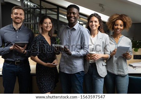 Portrait of happy successful multiracial business team standing with digital tablets, notebooks, ready to make notes. Smiling young motivated startup international employees group looking at camera.
