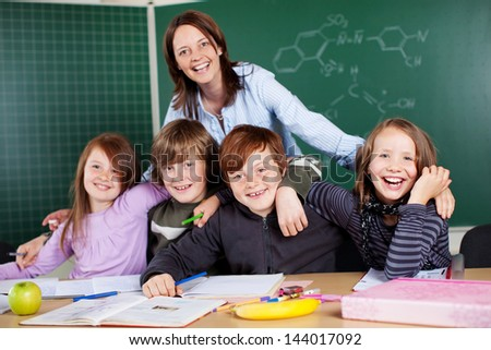 Portrait of happy teacher and her students inside the classroom