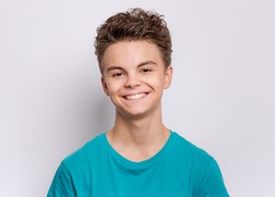 Portrait of happy teen boy in blue t-shirt in studio. Photo of adorable young smiling boy looking at camera on gray background.