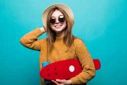 Portrait of happy teen girl in sunglasses posing with skateboard while standing and looking at camera isolated over green background