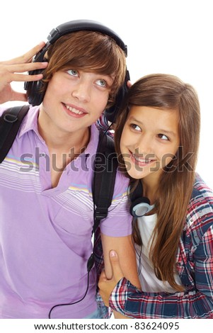 Portrait of happy teenage boy with headphones listening to music while his girlfriend near by trying to hear it