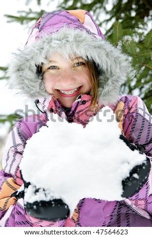Portrait of happy teenage girl holding snow in gloves