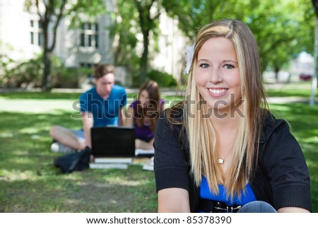 Portrait of happy teenage girl with classmates in background