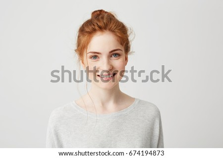 Portrait of happy tender ginger girl with blue eyes and freckles looking at camera smiling over white background. #674194873