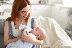 Portrait of happy tender young mother with ginger hair feeding her baby boy from milk bottle. Beautiful mom feeds infant son with formula while sitting on couch at home. Motherhood and happiness
