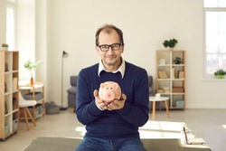 Portrait of happy thrifty mature man in glasses holding piggy bank, smiling and looking at camera. People and finance, successful business, planning budget, saving up money, good pension plan concept